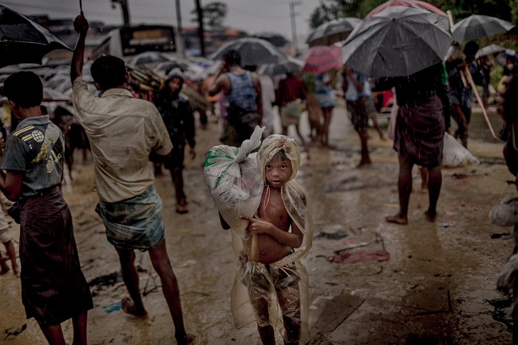 A kid carries relief aid and walks covered with plastic in the heavy rainfall. Balukhali Refugee Camp.