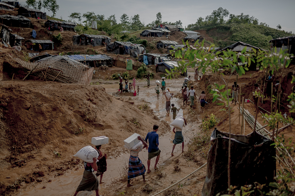 After collecting relief aid Rohingya refugees return to the make shift camp through the muddy camp road. Thyangkhali Refugee Camp, Cox's Bazar.
