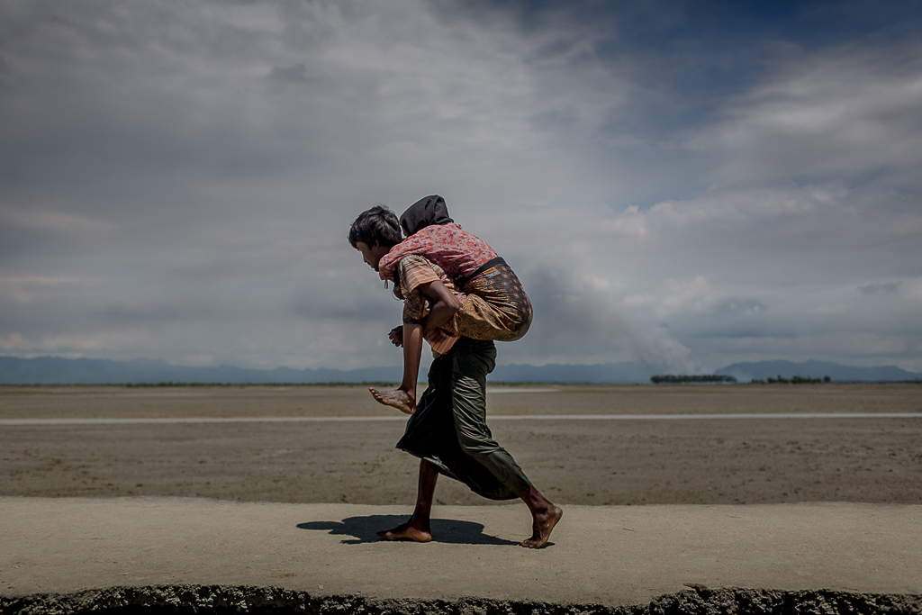 A Rohingya man, carrying his old mother on his back, proceed to the makeshift camps.