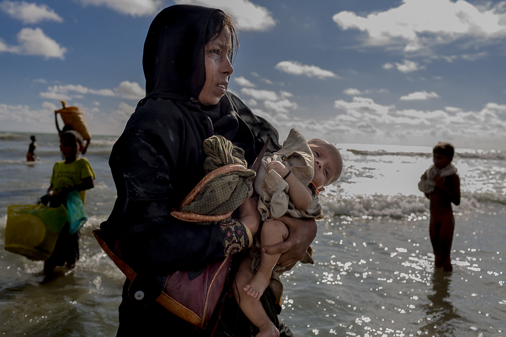 A Rohingya mother cries, holding her child on the shore of Bangladesh after crossing Myanmar-Bangladesh border by boat through the Bay of Bengal.