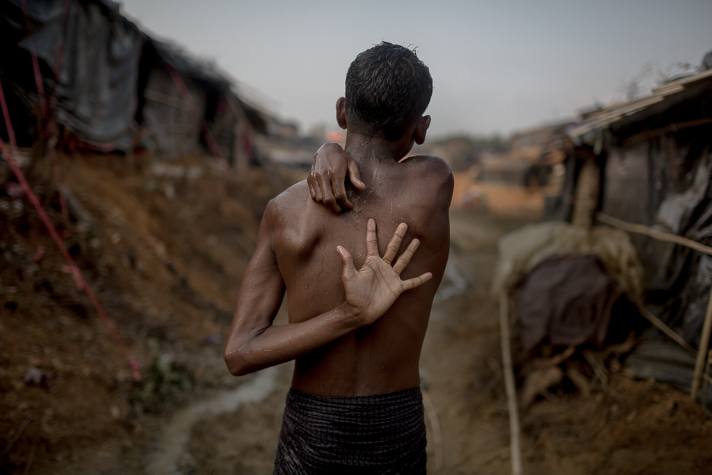 A Rohingya man washes his body with collected water inside the Thyangkhali camp.