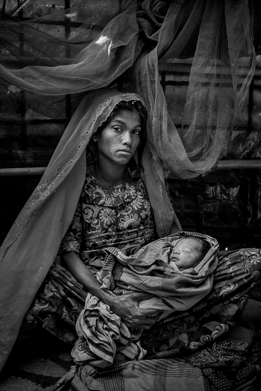 Rohingya mother Fatema from Jambuinna, Myanmar is holding her 7 days old newborn boy named Shahed. She gave birth in Kutupalong refugee camp, Cox's Bazar.